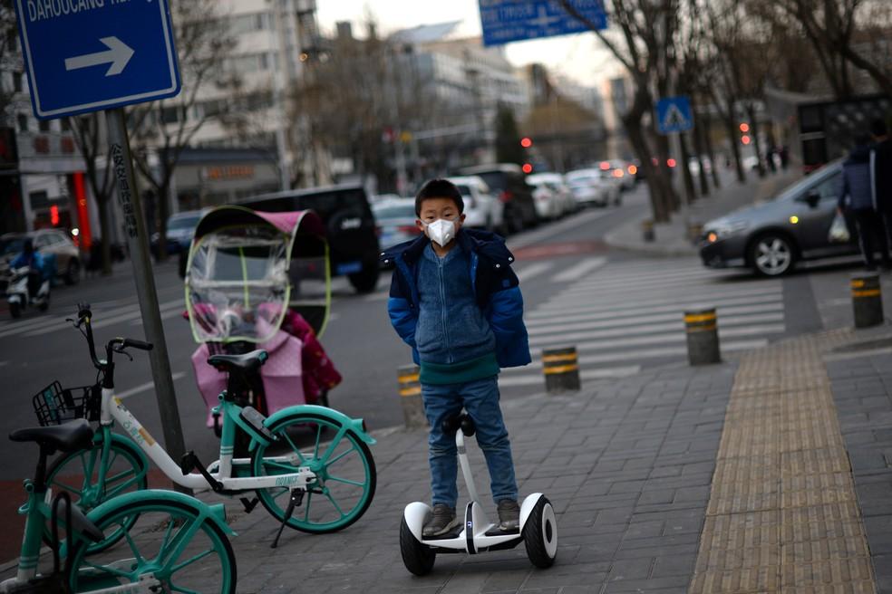 Criança usando uma máscara usa um scooter em Pequim, na China, nesta terça-feira (18). — Foto: Tingshu Wang/Reuters