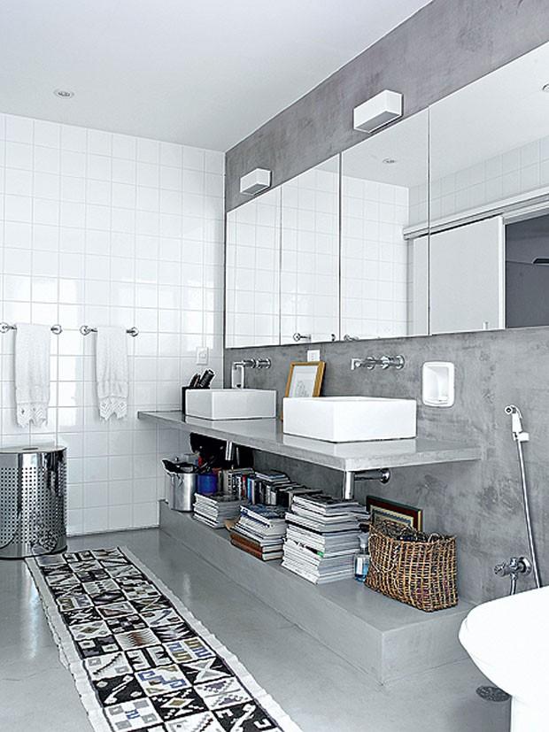Criado no recuo lateral, o banheiro do casal tem bancada de concreto, com duas cubas de apoio. Projeto de Claudia Haguiara (Foto: Christian Maldonado)