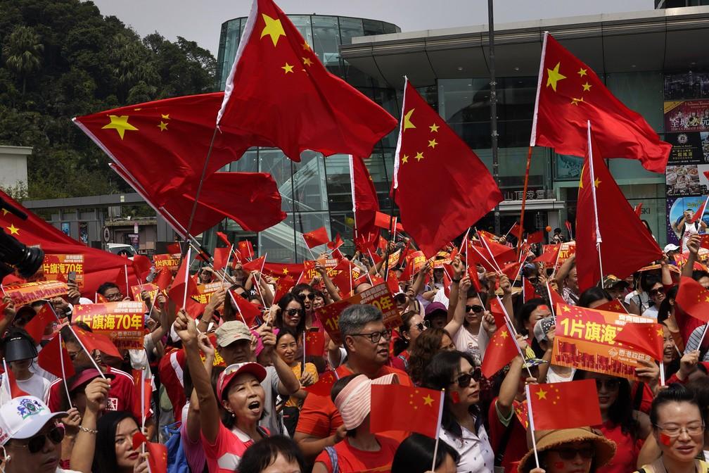 Manifestantes pró-China também foram às ruas de Hong Kong neste domingo (29), vestindo vermelho e carregando bandeiras chinesas. — Foto: Vincent Yu/AP