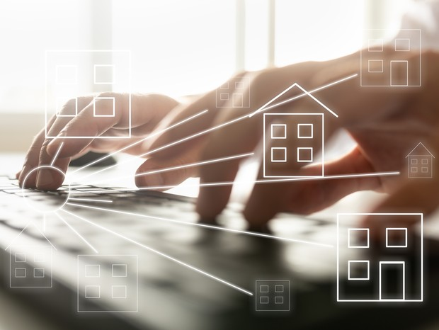 Online real estate concept - male hands typing on computer keyboard with house shaped icons over the image. (Foto: Getty Images/iStockphoto)