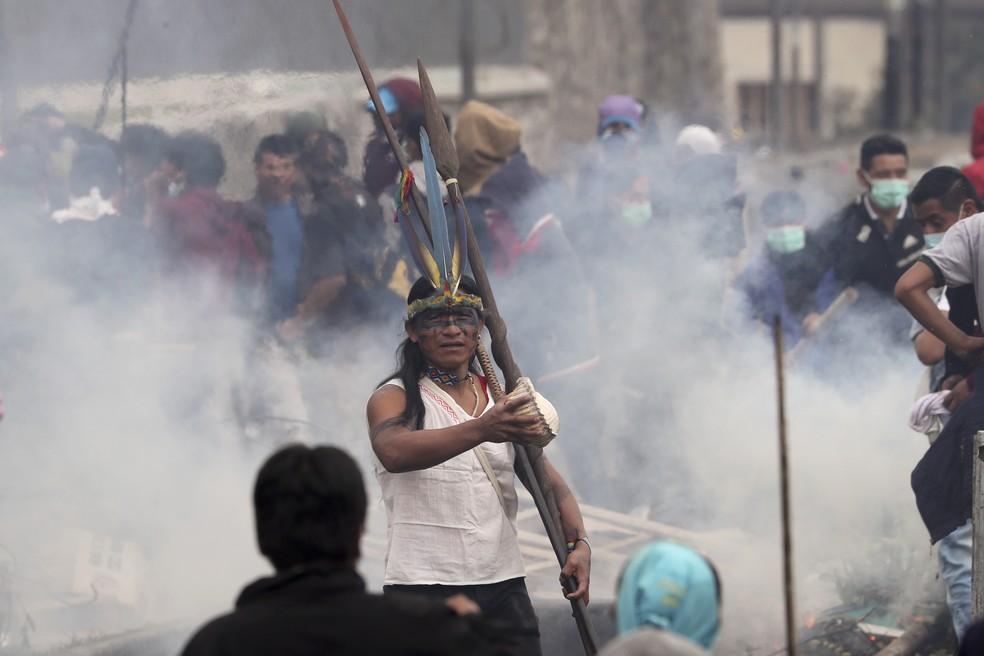 Manifestante indígena protesta contra o governo em meio a fumaça de gás lacrimogênio em Quito, no Equador, nesta sexta-feira (11) — Foto: Dolores Ochoa/AP Photo