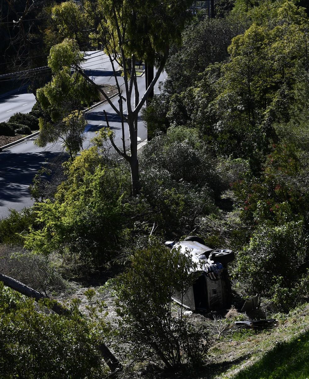 Carro do jogador Tiger Woods tombado fora da estrada — Foto: AFP/PAtrick Fallon