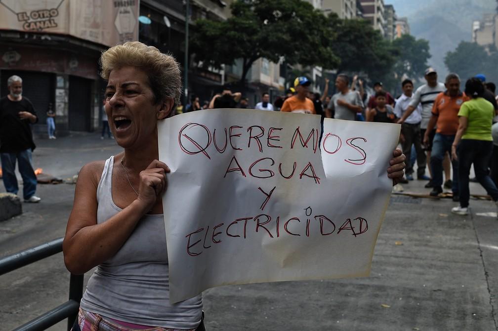 'Queremos água e eletricidade', diz cartaz de venezuelana que protesta em Caracas contra apagão na Venezuela — Foto: Federico Parra/AFP