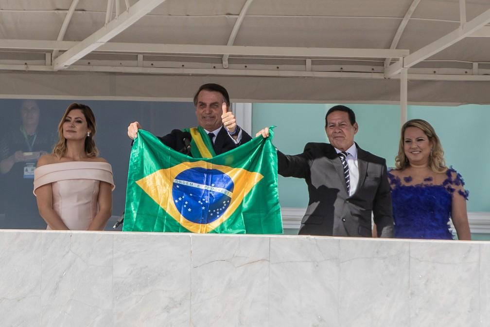 O presidente Jair Bolsonaro e o vice, Mourão, mostram uma bandeira do Brasil no Parlatório diante do público na Praça dos Três Poderes — Foto: Fábio Tito/G1