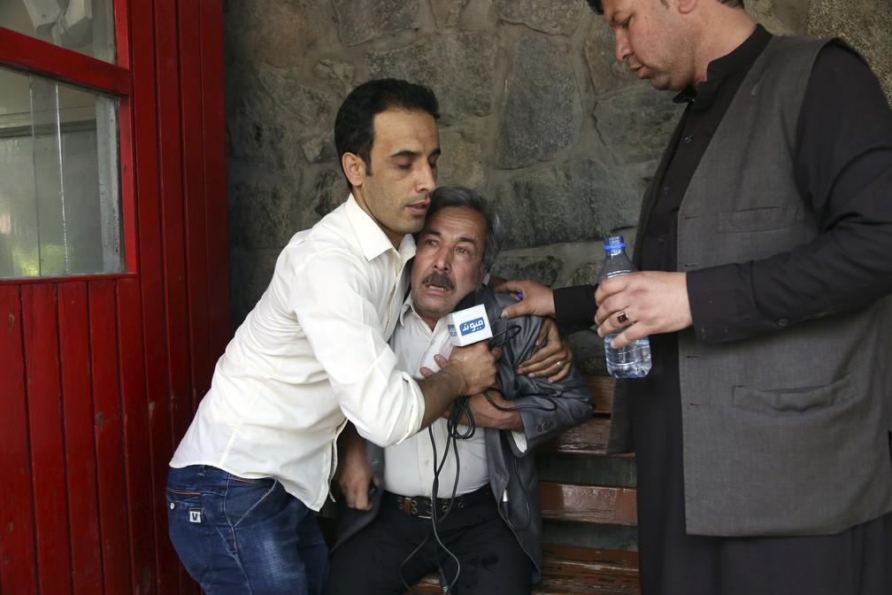 Pai de um dos jornalistas mortos é consolado no hospital em Cabul (Foto: Rahmat Gul/AP)