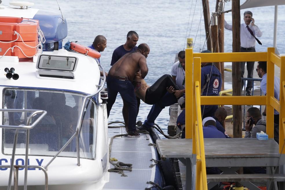 Vítima é socorrida após naufrágio ocorrido na manhã desta quinta-feira, 24, próximo à Ilha de Itaparica, na Bahia (Foto: Xando Pereira/Agência A Tarde/Estadão Conteúdo)