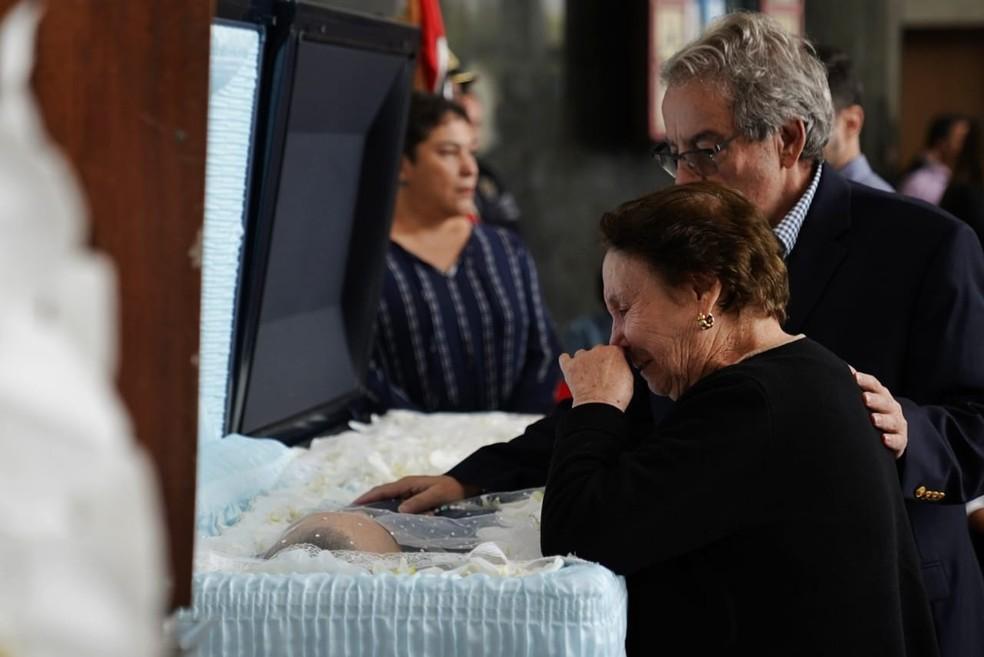 Mãe de Gugu, Maria do Céu, chora ao ver corpo do filho na Alesp. Ela chegou de cadeira de rodas no salão, mas foi caminhando com ajuda de uma bengala até o caixão.  — Foto: Marcelo Brandt/G1