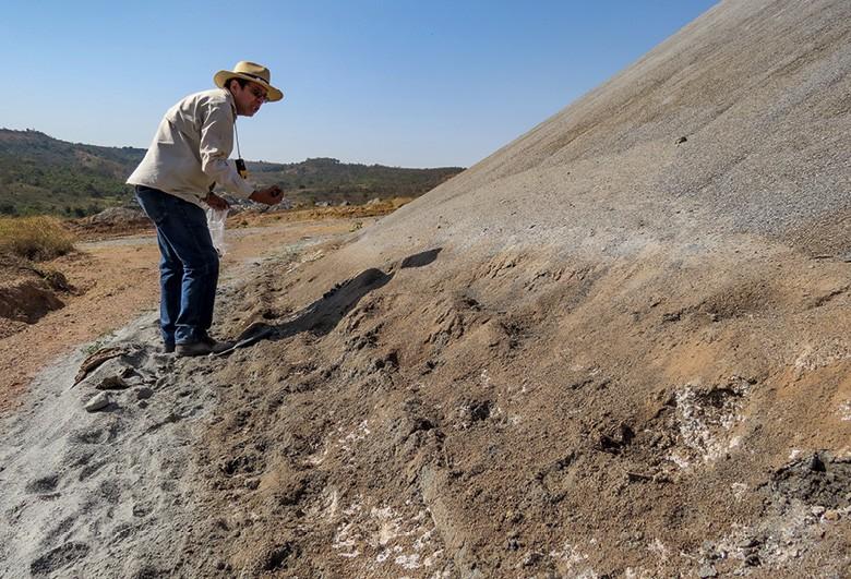 Eder Martins em um monte de pó de rocha de biotita xisto, em Abadiânia (GO) (Foto: Araci Molnar Alonso/Embrapa Cerrados)