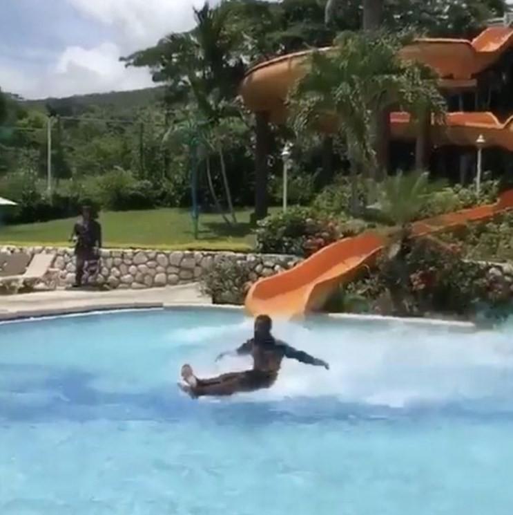 Homem desliza sobre a água de piscina em resort na Jamaica