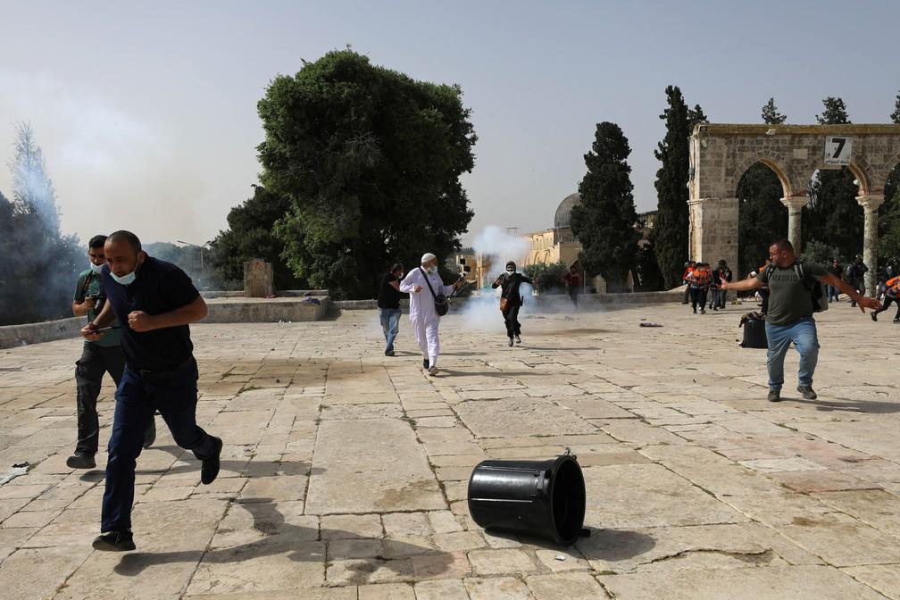 Palestinos fogem enquanto a polícia israelense dispara bombas de efeito moral durante confrontos no complexo que abriga a mesquita Al-Aqsa nesta segunda (10) — Foto: Ammar Awad/Reuters