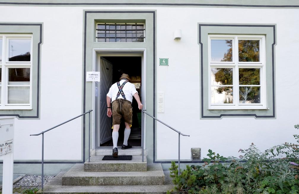 Homem usando vestimenta típica da Bavária entra em um local de votação em Benediktbeuern, na Bavária, sul da Alemanha, neste domingo (26). — Foto: Michaela Rehle/Reuters