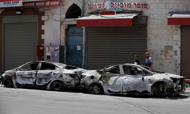Pedestres caminham perto de carros incendiados em Lod, nos arredores de Tel Aviv