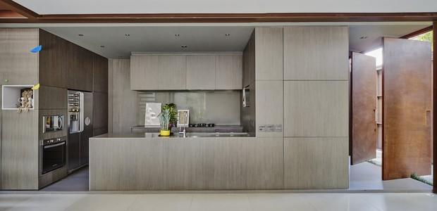 Integrada com a sala, a cozinha tem acabamento em tom de fendi e parece um volume  independente em meio ao projeto (Foto: Pedro Kok)