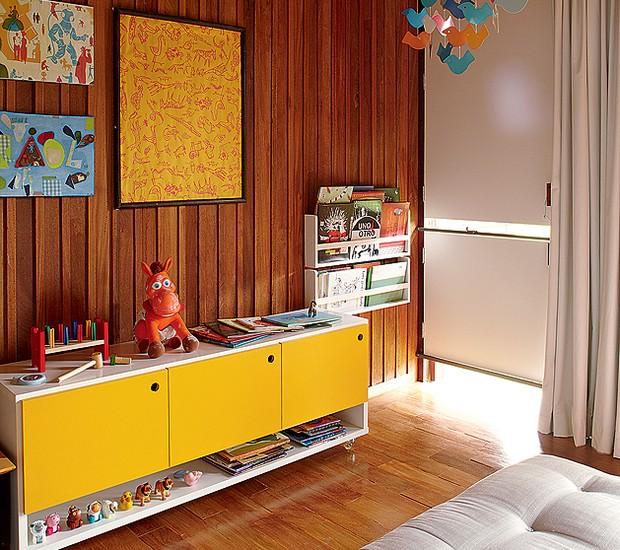 Um móvel do tipo rack acomoda os brinquedos de Raul, 2 anos, filho de Graziella Mattar. As portas escondem a bagunça, enquanto em cima e embaixo algumas peças enfeitam o quarto. Os livros têm espaço especial ao lado (Foto: Victor Affaro/Casa e Jardim)