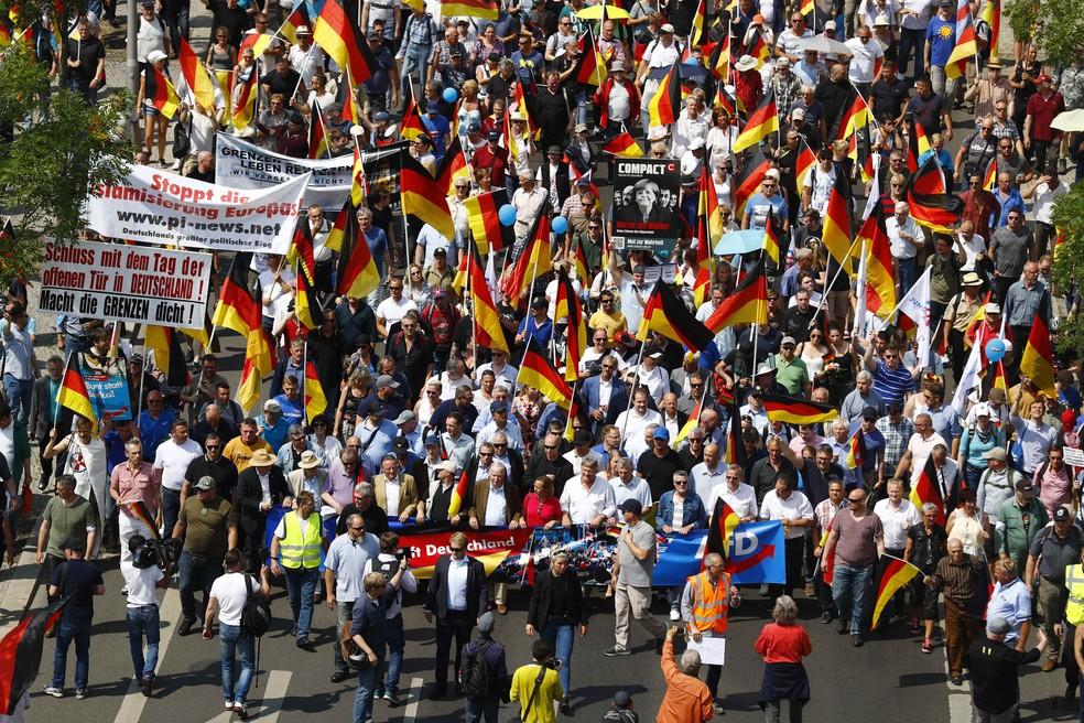 Partidários do partido anti-imigração Alternativa para a Alemanha (AfD) seguram bandeiras alemãs durante manifestação em Berlim em 2018. — Foto: REUTERS/Hannibal Hanschke