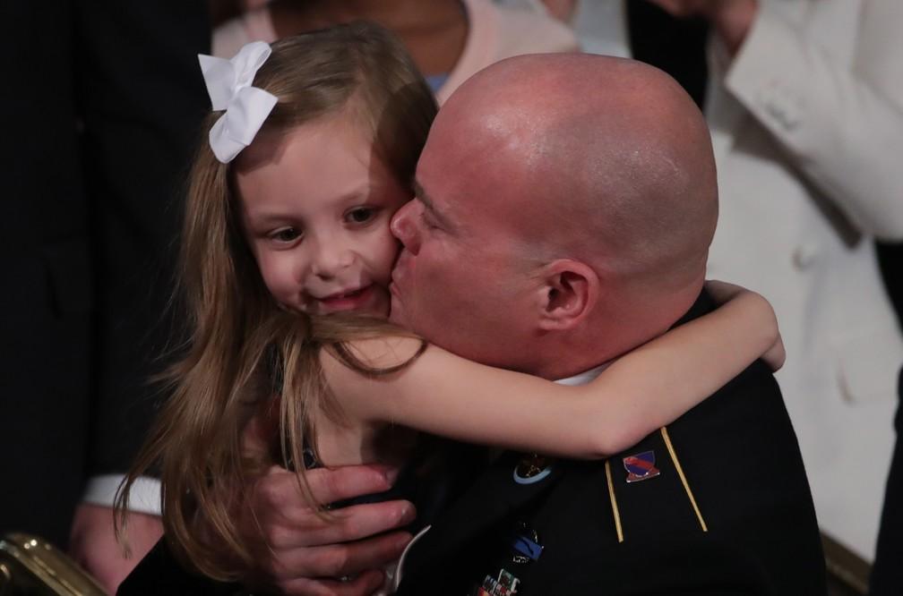 Townsend Williams, sargento norte-americano, abraça a filha ao aparecer de surpresa no discurso de Donald Trump na Câmara dos EUA. O militar estava no Afeganistão e foi apresentado pelo presidente nesta terça-feira (4) — Foto: Tom Brenner/Reuters