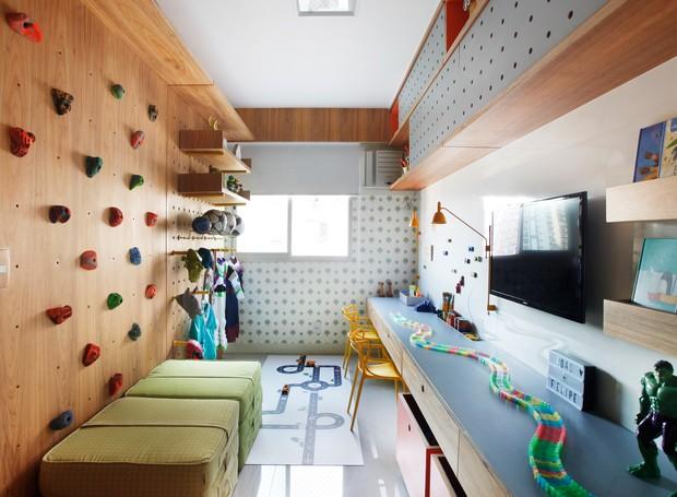 O papel de parede com estampa delicada de árvores, da Orlean,na parede do fundo da brinquedoteca, foi o contraponto à marcenaria nos tons laranja, verde cítrico e cinza azulado, desenhada pelas arquitetas (Foto: Divulgação)