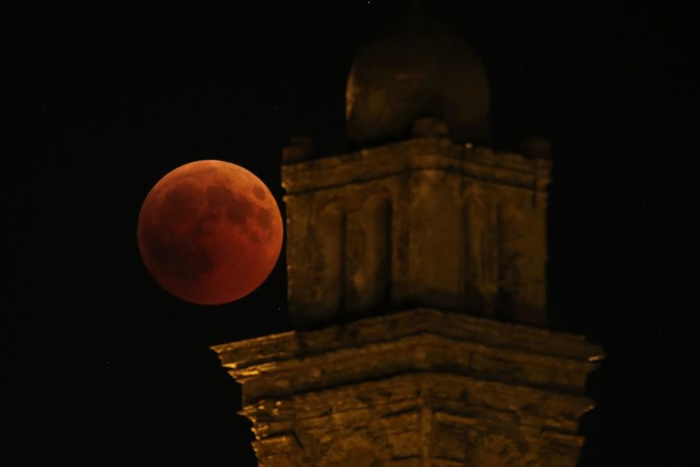 Eclipse com lua de sangue visto perto da torre de igreja em Venzolasca, França. (Foto: PASCAL POCHARD-CASABIANCA / AFP)
