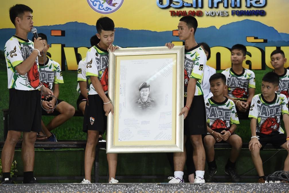 Jovens que ficaram presos em caverna prestam homenagem ao mergulhador que morreu na operação de resgate, na primeira aparição do grupo após alta de hospital nesta quarta-feira (18) (Foto: Lillian Suwanrumpha/AFP)