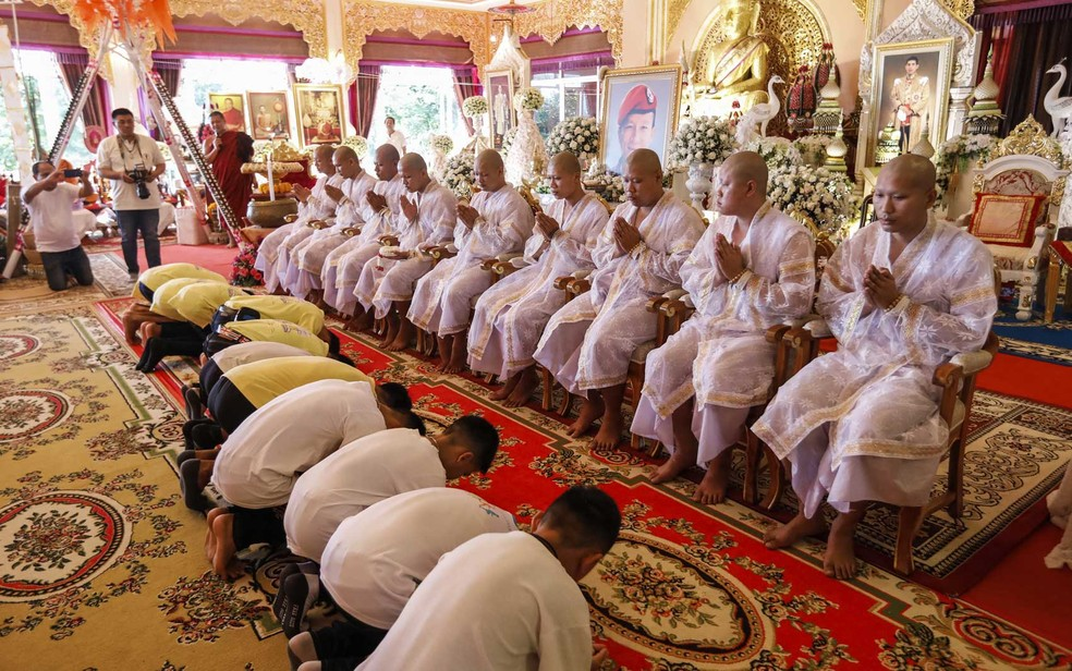 Garotos tailandeses se curvam diante de novos monges budistas durante cerimônia em um templo em Chiang Rai (Foto: Krit Phromsakla Sakolnakorn / Thai News Pix / via AFP Photo)