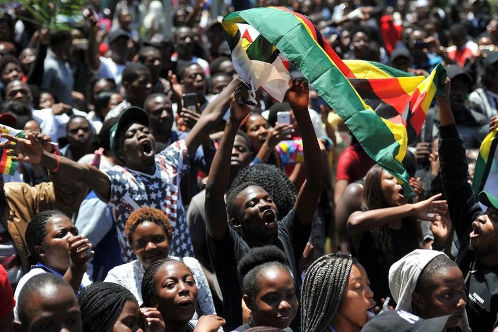 Homem segura bandeira do Zimbábue em protesto contra o título de doutora em filosofia concedido à mulher do presidente Robert Mugabe, Grace, nesta segunda-feira (20)  (Foto: AFP)