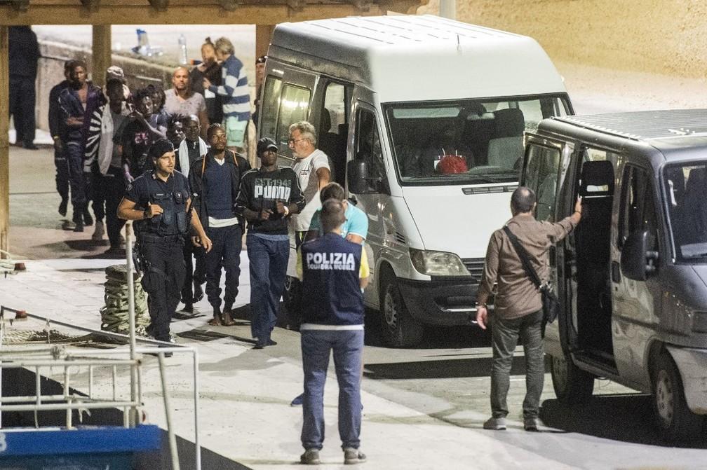Migrantes entram em vans depois de depois de desembarcar do navio 'Ocean Viking', neste sábado (14), na Itália — Foto: Alessandro Serrano/AFP