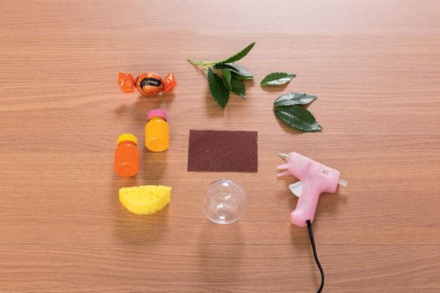 1. Materiais: Chocolate | Folhas artificiais | Tinta PVA amarela e laranja | Lixa | Esponja | Bola de acrílico (tipo as de Natal) | Cola quente (Foto: Bruno Marçal / Editora Globo)