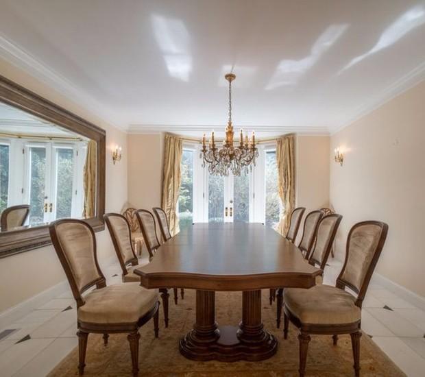 A sala de jantar possui móveis de madeira e portas, que trazem iluminação natural (Foto: The MLS/ Reprodução)