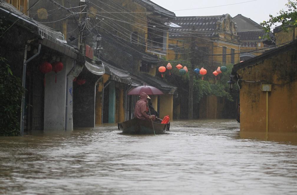 Habitantes da cidade histórica de Hoi An, tombada pela Unesco, usam barcos para se deslocar após passagem do tufão Damrey (Foto: Hau Dinh/AP)