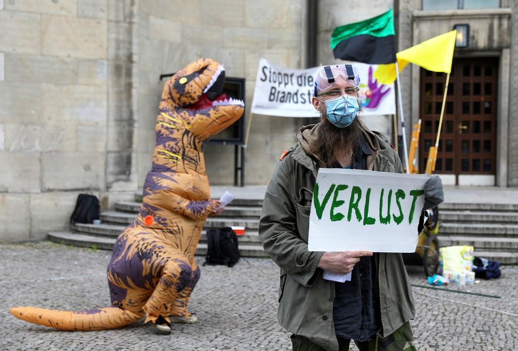 Manifestante com máscara e óculos de proteção segura cartaz escrito 'Derrota', durante protesto no Dia Internacional do Trabalho, em Berlim, na Alemanha — Foto: Christian Mang/Reuters