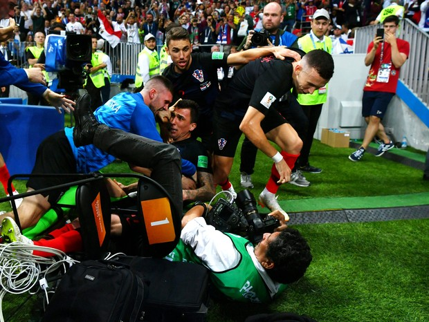 MOSCOW, RUSSIA - JULY 11:  Croatia players knock over a photographer as they celebrate after Mario Mandzukic of Croatia scores their team's second goal during the 2018 FIFA World Cup Russia Semi Final match between England and Croatia at Luzhniki Stadium  (Foto: Getty Images)
