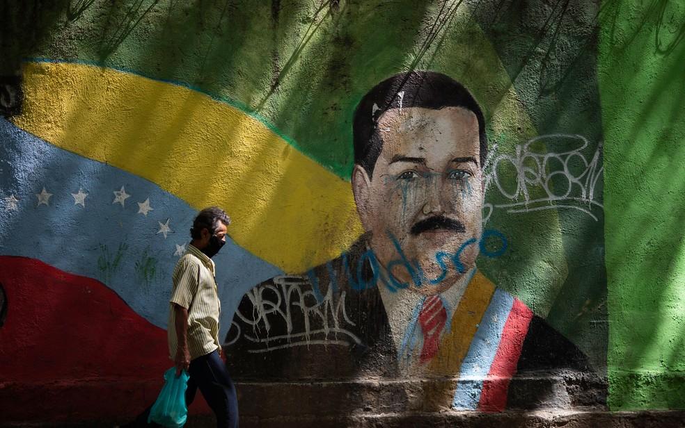 Homem passa em frente a um mural com o rosto de Nicolás Maduro, em Caracas, na Venezuela, em foto de 22 de julho — Foto: AP Photo/Ariana Cubillos