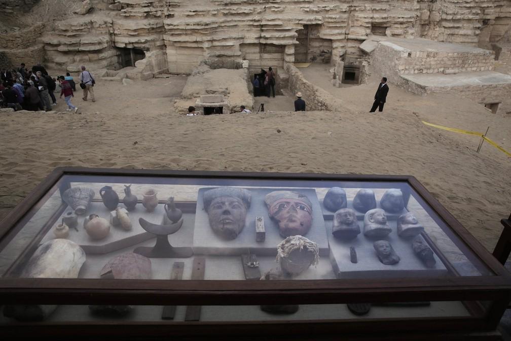 Artefatos em exposição em uma caixa de vidro em frente às tumbas recém-descobertas na necrópole em Sacará. — Foto: Nariman El-Mofty/AP