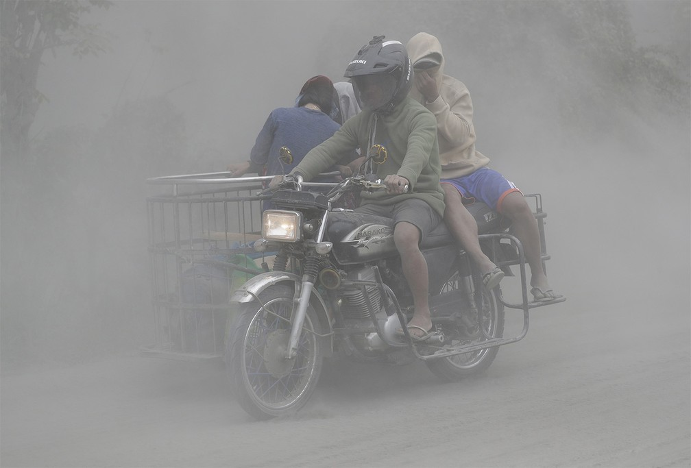 Pessoas de moto passam por rua coberta de cinzas em Tagaytay, na província de Cavite, nas Filipinas — Foto: Aaron Favila/AP