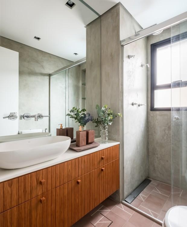 BANHEIRO | O espelho amplo cobre a parte de cima dos gabinetes. A estampa contemporânea dos ladrilhos hidráulicos da cozinha é repetida no piso, mas na cor rosa (Foto: Nathalie Artaxo/ Divulgação)