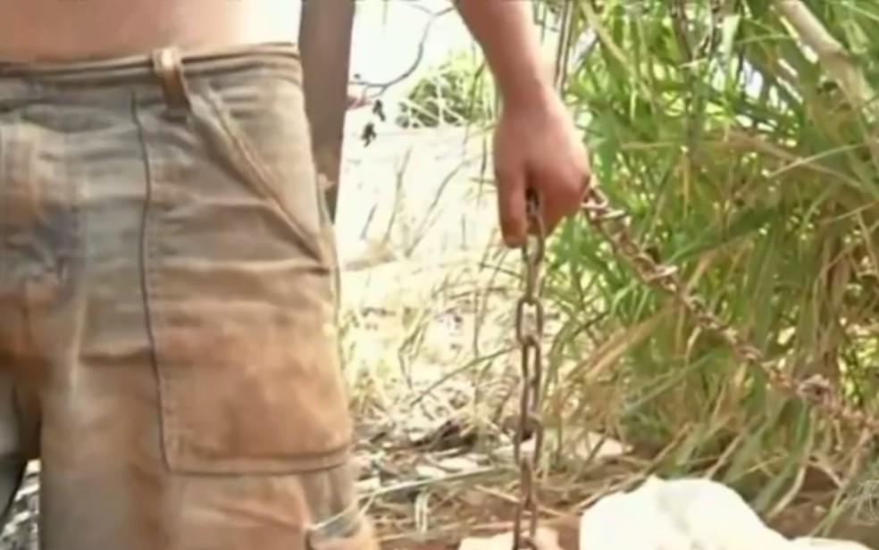 Jovem que teria problemas mentais é encontrado acorrentado a uma árvore no quintal de casa (Foto: Reprodução/TV Anhanguera)