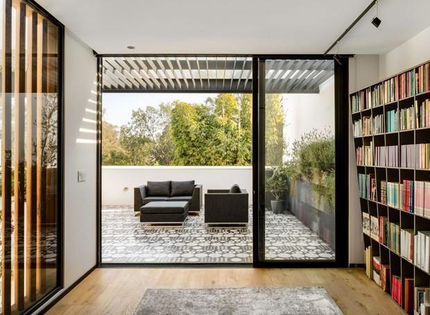 Também voltado para o terraço, um escritório é mobiliado por estantes recheadas de livros e divisórias que brincam com a entrada de luz (Foto:  Rafael Gamo/ Reprodução)