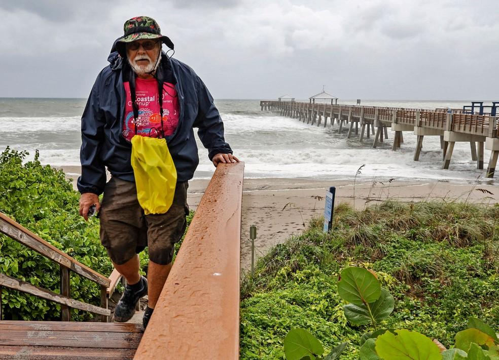 Homem sobe escada perto do píer da praia de Juno, na Flórida, na segunda-feira (2), enquanto o furacão Dorian se aproxima da costa americana  — Foto: Carl Juste / Miami Herald via AP