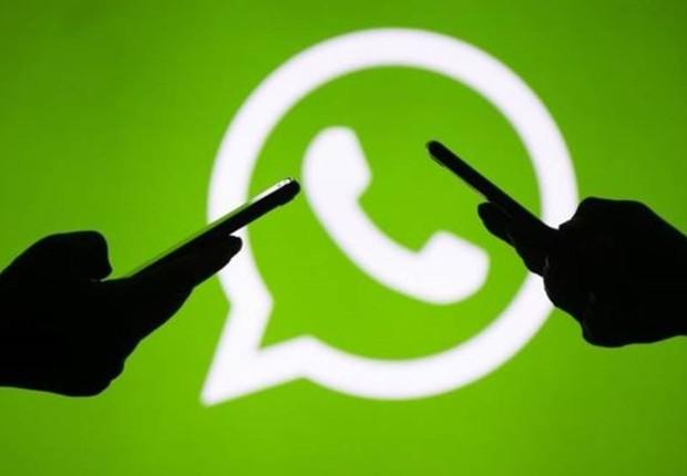 Logo do WhatsApp com duas mãos usando smartphones (Foto: Getty Images via BBC)