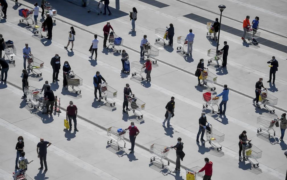 Italianos fazem fila em supermercado de Milão neste sábado (11), véspera da Páscoa, mas respeitando a distância — Foto: Claudio Furlan/LaPresse via AP