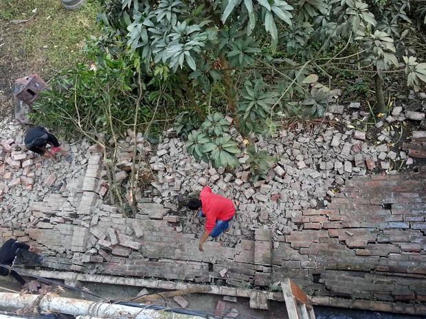 Pessoas trabalham na parede externa de uma casa que desmoronou em Imphal (Foto: Yurreipem Arthur / AP Photo)