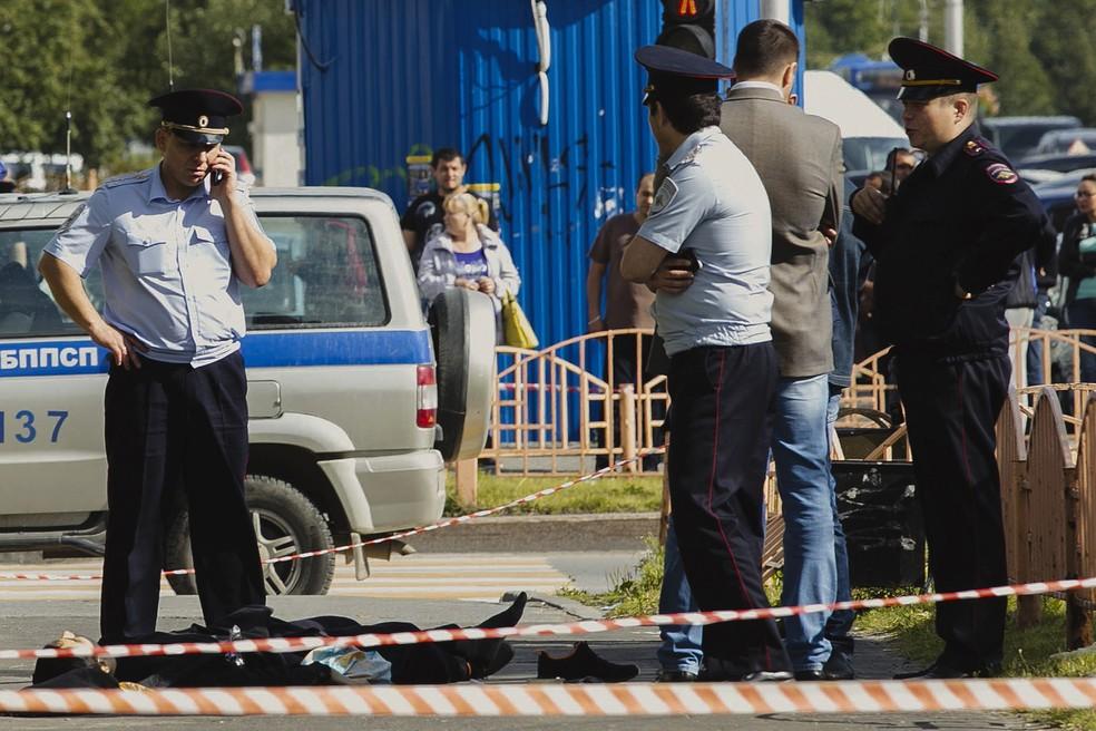 Policiais ao lado do corpo do homem que feriu pessoas com faca em Surgut, na Rússia (Foto: Irina Shvets/Siapress.ru via AP)