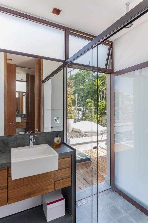 banheiro com box de vidro, bancada de cimento queimado com cuba de sobrepor branca, armário de madeira, espelho quadrado e piso cinza.