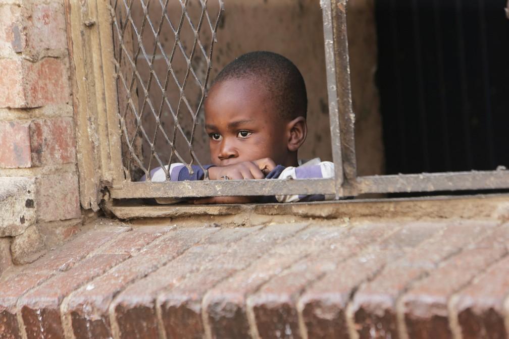 Uma criança olha para a rua da janela de sua prédio em Harare, no Zimbábue, em 30 de março. O país está em isolamento por 21 dias em um esforço para conter a propagação do coronavírus — Foto:  Tsvangirayi Mukwazhi/AP