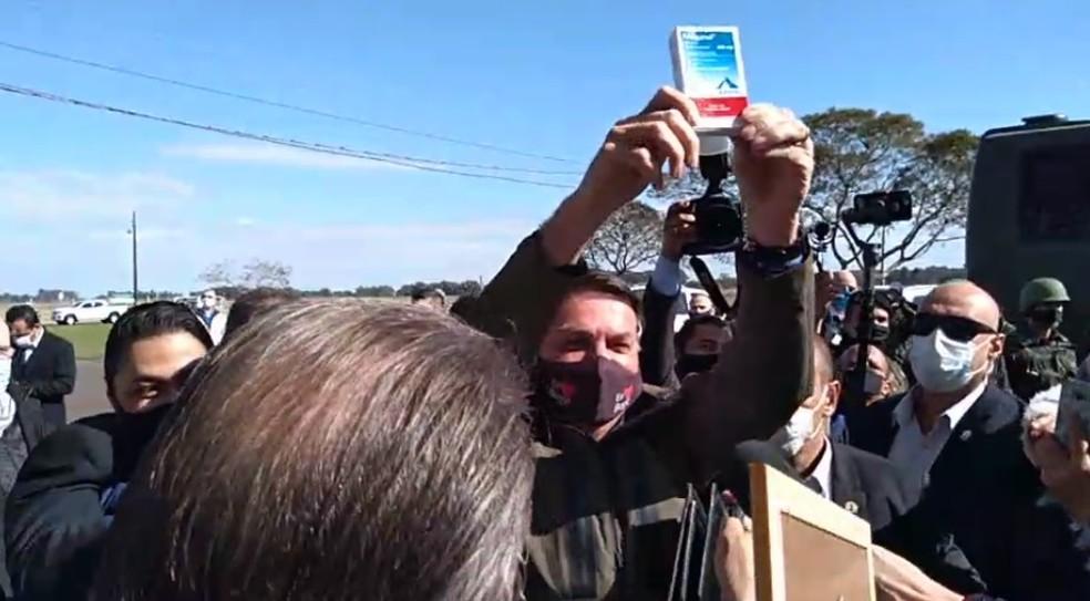 Bolsonaro mostra cloroquina ao chegar em aeroporto de Bagé.  — Foto: Reprodução/RBS TV