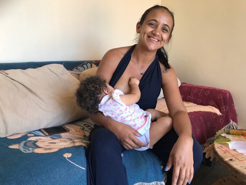Maria de Jesus, fundadora da creche Alecrim, amamenta a filha caçula durante entrevista (Foto: Marília Marques/G1)