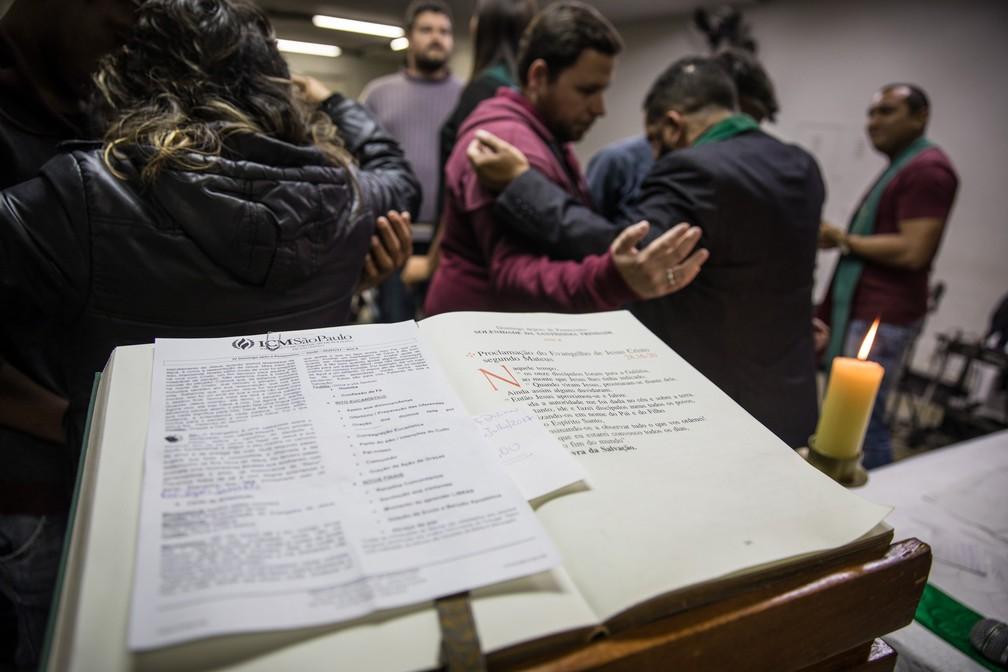 Pessoas se abraçam em oração ao fim de um culto inclusivo na igreja do reverendo Cristiano Valério, em São Paulo (Foto: Fábio Tito/G1)