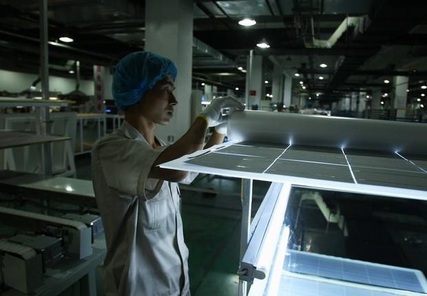 Trabalhador chinês em fábrica de painéis solares. (Foto: Feng Li/Getty Images)