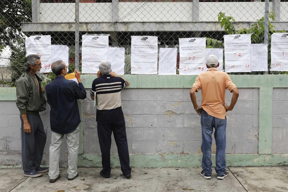 Eleitores conferem salas de votação nas eleições deste domingo (10) na Venezuela (Foto: Carlos Jasso/Reuters)
