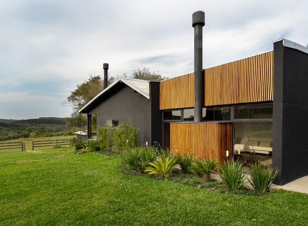 O preto das paredes e a madeira criam um contraste elegante com o verde natural. Esquadrias da Moldulyne Portas e janelas em PVC (Foto: Roberta Gewehr / Divulgação)